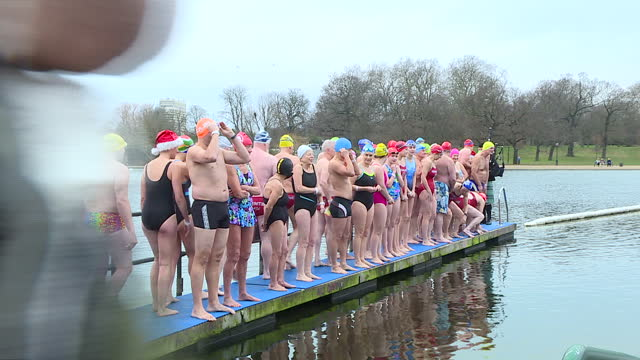 exterior shots of people lining up on pier of the serpentine jump in the water to swim the the serpentine swimming club's christmas morning handicap... - the serpentine london stock videos & royalty-free footage