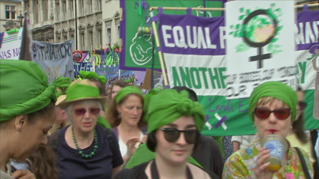 Exterior shots of people marching wearing suffragette colours of green white and violet holding 'equal pay' placards and banners and walking past a...