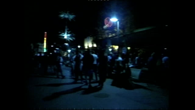 Exterior shots of people on San Antonio beachfront walking past various bars and clubs at night time on 30 June 2001 in Ibiza Spain