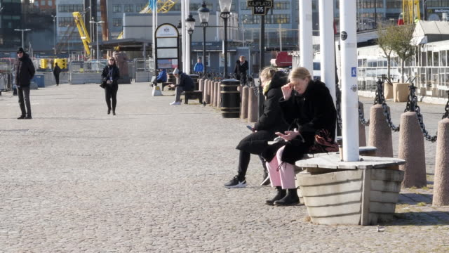 exterior shots of people outside a cafe on stockholms ström and strolling along the marina on 3 april 2020 in stockholm, sweden - schweden stock-videos und b-roll-filmmaterial