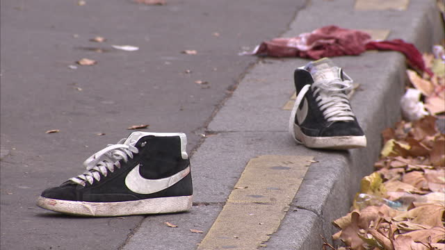exterior shots of people outside the bataclan theatre in the wake of the paris terror attacks, with the discarded and bloody items of some of the... - våld bildbanksvideor och videomaterial från bakom kulisserna