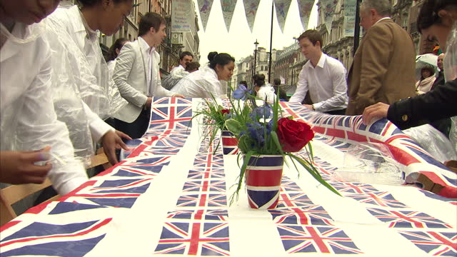exterior shots of people preparing for piccadilly jubilee street party cleaning and wiping down tables burgers being cooked by chefs and union flag... - street party stock videos and b-roll footage