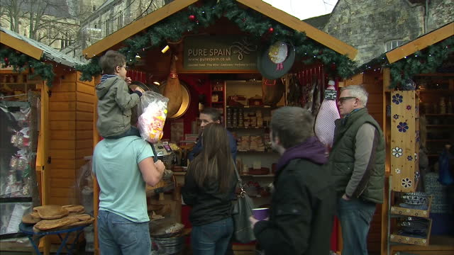 exterior shots of people queueing to buy crepes and bratwurst and browsing at a stall selling spanish food and cooking equipment at a christmas... - 英国ハンプシャー点の映像素材/bロール