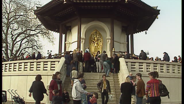 exterior shots of people queuing to lay tribute flowers at the peace pagoda in battersea park for the victims of the dunblane primary school... - バタシー点の映像素材/bロール