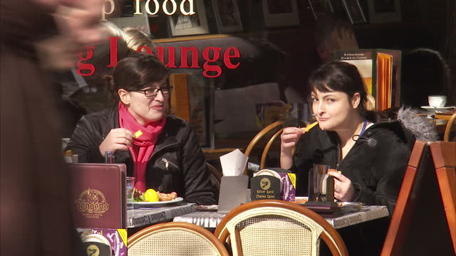 Exterior shots of people relaxing in the historic city centre of Brussels many eating chips waffles and ice creams on March 04 2010 in Brussels...