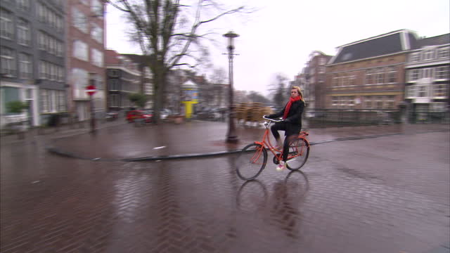 Exterior shots of people riding bicycles along canalsides on a rainy day in Amsterdam on March 16 2010 in Amsterdam Netherlands
