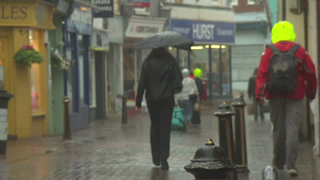 vidéos et rushes de exterior shots of people running and walking down the streets of cowes during heavy rain>> on august 10 2014 in various cities united kingdom - cowes