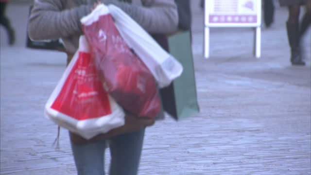 vídeos de stock, filmes e b-roll de exterior shots of people shopping and carrying high street shop carrier bags as they shop for christmas presents on december 16, 2014 in norwich,... - high street