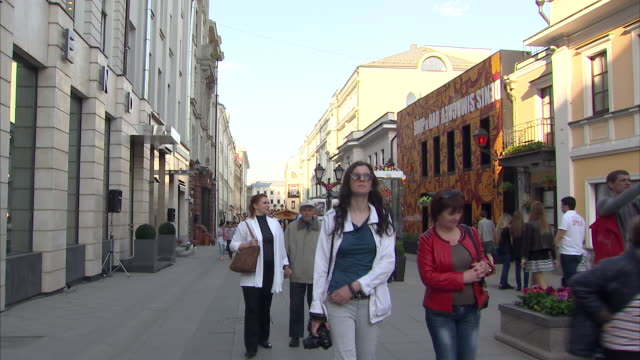 exterior shots of people shopping and luxury designer brand shops including tag heuer, prada and louis vuitton in moscow, russia - デザイナー服点の映像素材/bロール