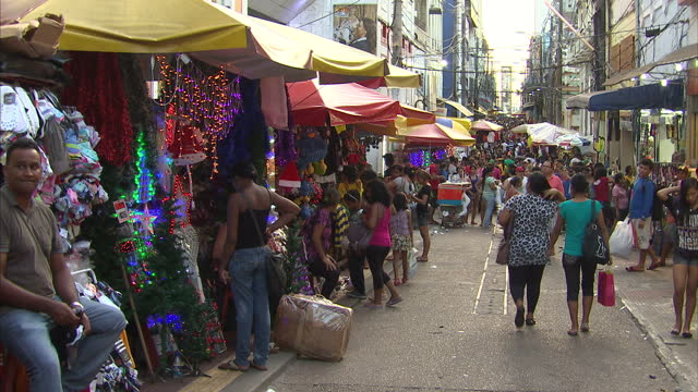 vidéos et rushes de exterior shots of people shopping, browsing through stalls of clothes and other goods at a market in manaus. manaus market and boats on the rio negro... - amérique du sud