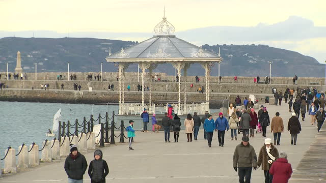 Exterior shots of people strolling along Dun Laoghaire harbour sailing boats in harbour harbour walls a lighthouse and a Victorian bandstand on 26...