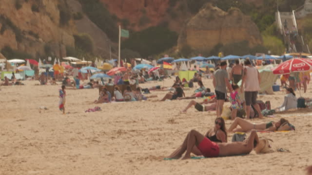 exterior shots of people sunbathing, swimming etc on the beach at praia da luz and beach umbrellas and beachfront restaurants on 11 september 2020 in... - madeleine mccann stock videos & royalty-free footage