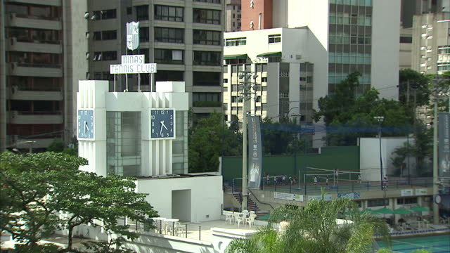 exterior shots of people swimming and playing volleyball at the minas tennis club with views of the belo horizonte skyline build up to 2014 world cup... - internationaler fußball stock-videos und b-roll-filmmaterial