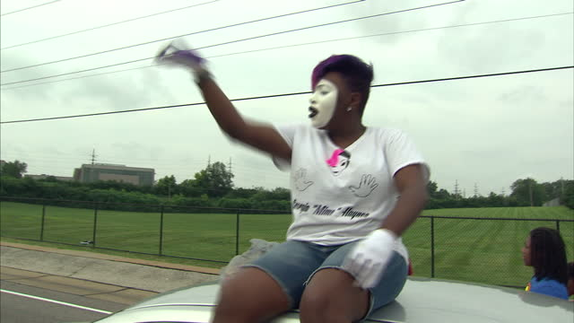 Exterior shots of people taking part in a protest parade through the streets of Ferguson chanting 'Don't Shoot' some with faces painted white on...