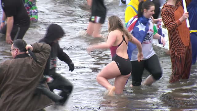 Exterior shots of people taking part in the annual Loony Dook many wearing fancy dress while wading and taking photographs in the Firth of Forth>> on...