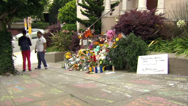 vídeos de stock e filmes b-roll de exterior shots of people taking photographs on mobile phones and looking at tributes to the late actor robin williams outside the home where the... - robin williams ator