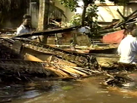 vídeos de stock, filmes e b-roll de exterior shots of people wading through flood waters walking past damaged buildings broken homes and piles of rubble left by tsunami wave boxing day... - oceano índico