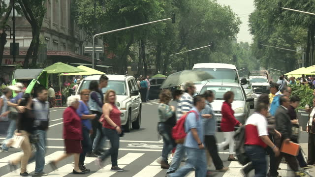 exterior shots of people walking across a busy road and along pavements in the centre of mexico city on june 23, 2015 in mexico city, mexico. - 国境点の映像素材/bロール
