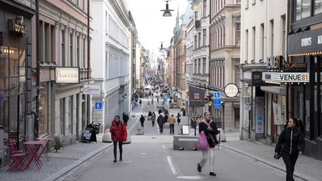 exterior shots of people walking along a busy pedestrianised shopping street on 3 april 2020 in stockholm, sweden - svezia video stock e b–roll