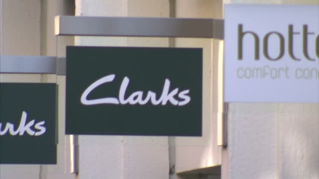 exterior shots of people walking along a pedestrianised shopping street in cambridge, and signage outside various shops including hotel chocolat,... - high street stock-videos und b-roll-filmmaterial