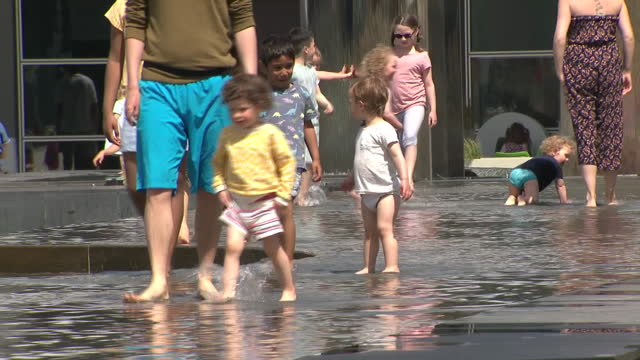 exterior shots of people walking along bristol docks, people boating and children playing in a water fountain on bank holiday weekend on the 30th may... - fountain stock videos & royalty-free footage