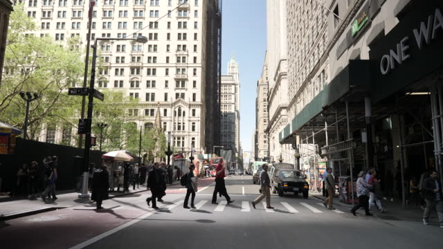 exterior shots of people walking along pavements and traffic passing an intersection in manhattan on 10 may 2019 in new york, united states - gelbes taxi stock-videos und b-roll-filmmaterial