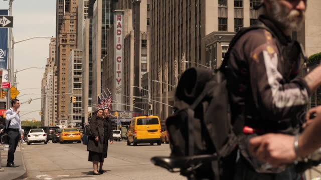 exterior shots of people walking along pavements and traffic passing an intersection near the rockerfeller center and radio city music hall on 10 may... - gelbes taxi stock-videos und b-roll-filmmaterial