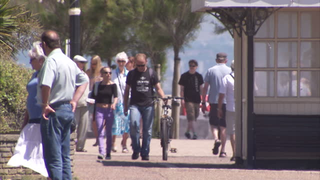 exterior shots of people walking along worthing promenade, sunbathing on the beach and sat outside a restaurant in the sunshine on 10 july 2015 in... - worthing点の映像素材/bロール