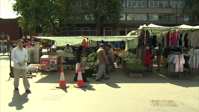 vídeos de stock, filmes e b-roll de exterior shots of people walking and browsing through a street market in poplar, including many members of the asian and muslim communities.>> on... - east asian ethnicity