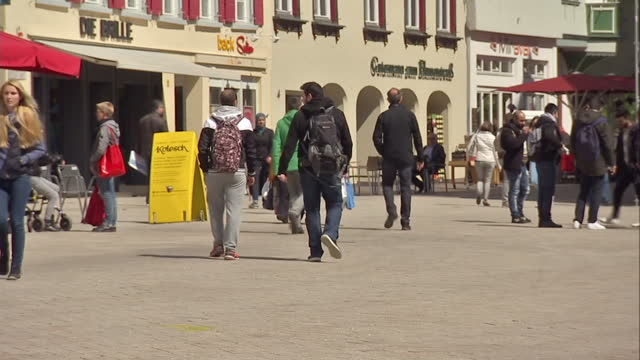 Exterior shots of people walking around and relaxing in chairs in Biberach town square including traditional Bavarian architecture and a clock tower...
