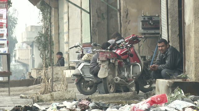 Exterior shots of people walking cycling and playing football on the streets of Aleppo Piles of rubbish and debris lie at the sides of the road>> on...