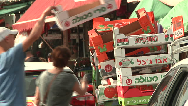 exterior shots of people walking on pavements and market traders stacking boxes at a busy fruit market in ashkelon on march 17 2015 in ashkelon israel - ashkelon stock videos and b-roll footage