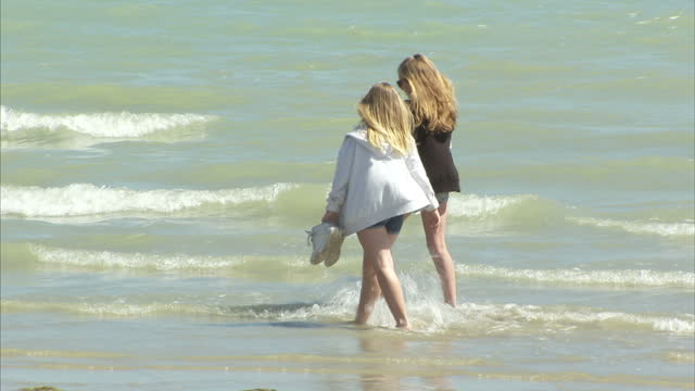 exterior shots of people walking on worthing beach and paddling in the sea on 10 july 2015 in worthing, united kingdom - worthing点の映像素材/bロール