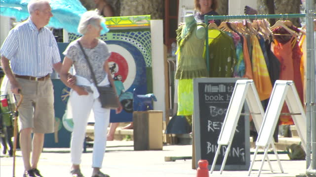 exterior shots of people walking on worthing promenade past various stalls selling arts and crafts item on a sunny day on 10 july 2015 in worthing,... - worthing点の映像素材/bロール
