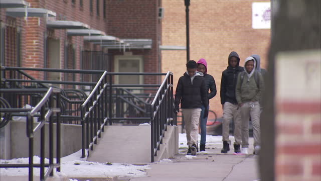 stockvideo's en b-roll-footage met exterior shots of people walking past boarded up abandoned homes and kids playing on the icy pavements on march 15 2017 in baltimore md united states - maryland staat