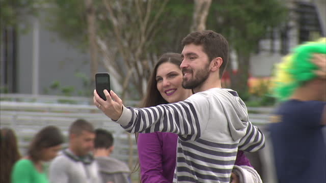 exterior shots of people walking past maracana stadium and through the olympic village taking photos selfies on august 12 2016 in rio de janeiro... - 記号点の映像素材/bロール