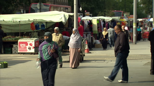 exterior shots of people walking through a street market in poplar including many people from the muslim and asian communities>> on august 20 2014 in... - multiracial group stock videos & royalty-free footage