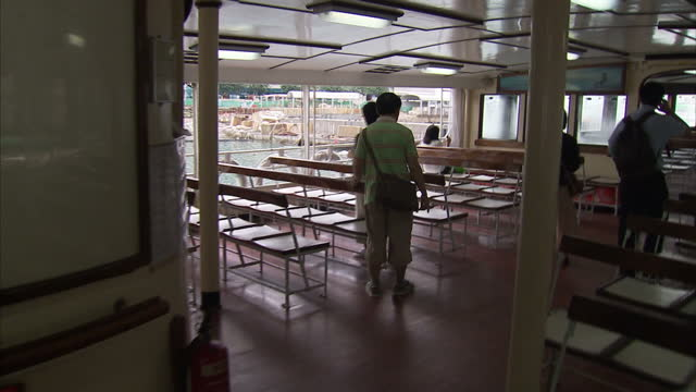 Exterior shots of people walking through Ferry terminal harbour and onto ferry boat taking seats Passengers board ferry boat in Hong Kong harbour on...