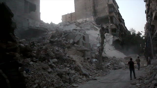 Exterior shots of people walking through street covered in rubble in the aftermath of an airstrike on September 22 2016 in Aleppo Syria