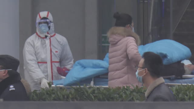 exterior shots of people wearing hygiene face masks ambulances with sirens and blue lights flashing person wearing face mask hair covering and... - wuhan stock-videos und b-roll-filmmaterial