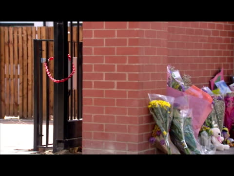 Exterior shots of photos and floral tributes left against a wall where six year old Semelia Campbell died after getting stuck in a set of electronic...