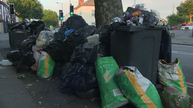 exterior shots of piled up rubbish bins that are overflowing with uncollected rubbish due to the refuse worker strike in birmingham people walk past... - bin bag stock videos & royalty-free footage