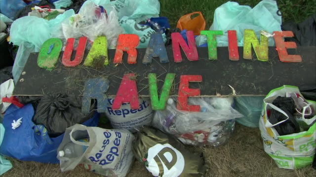 exterior shots of piles of rubbish and a sign reading 'quarantine rave' after an illegal rave in oldham on 24 june 2020 in manchester united kingdom - clubs besuchen stock-videos und b-roll-filmmaterial