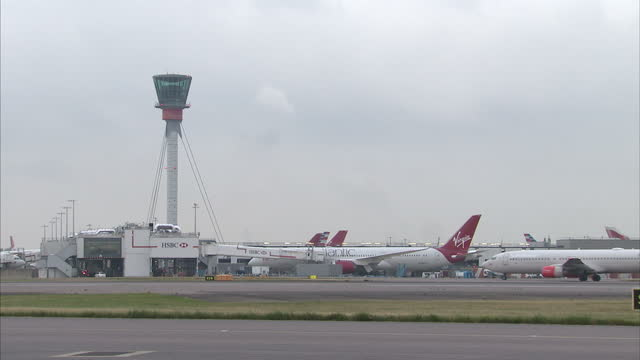 exterior shots of planes at heathrow airport including shots of virgin atlantic planes parked at gates a brussels airlines plane landing and british... - ヒースロー空港点の映像素材/bロール