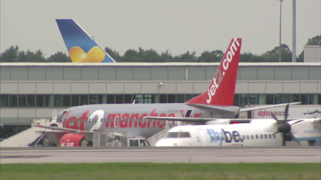 stockvideo's en b-roll-footage met exterior shots of planes parked at manchester airport including jet 2 us airways and flybe on july 31 2014 in manchester england - us airways