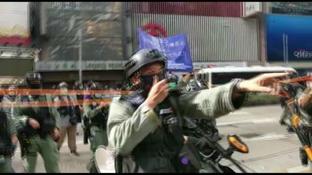 vídeos y material grabado en eventos de stock de exterior shots of police in riot gear speaking to crowds of protesters through a loud speaker on 1st july 2020 in hong kong, - manifestante