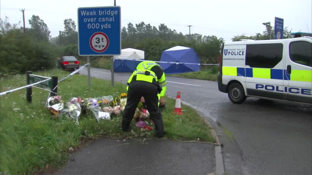 exterior shots of police laying flowers at the scene of the murder of pc andrew harper on 16 august 2019 in sulhamstead berkshire - monumento commemorativo temporaneo video stock e b–roll