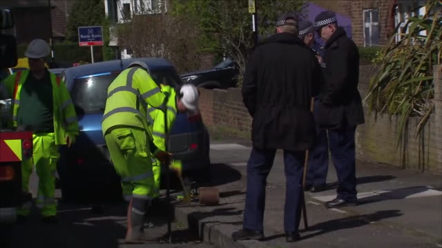 Exterior shots of police looking on as workers remove a parked car to allow access to search a drain in South Park Crecent Hither Green near the...