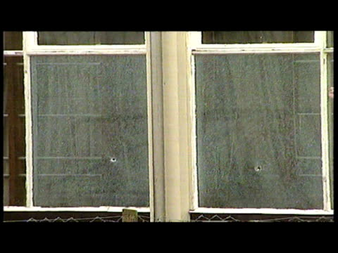 exterior shots of police officer leading reporters press towards school building exterior shots of bullet holes in gymnasium window including close... - ダンブレーン点の映像素材/bロール