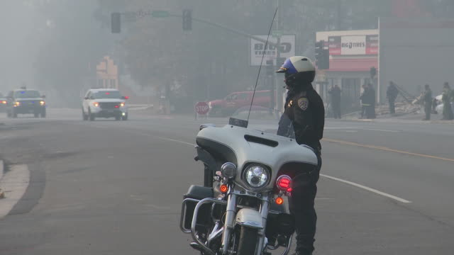 vídeos de stock e filmes b-roll de exterior shots of police officer standing on a side of the road with president trump's motorcade driving by on 17 november 2018 in paradise,... - nevoeiro fotoquímico